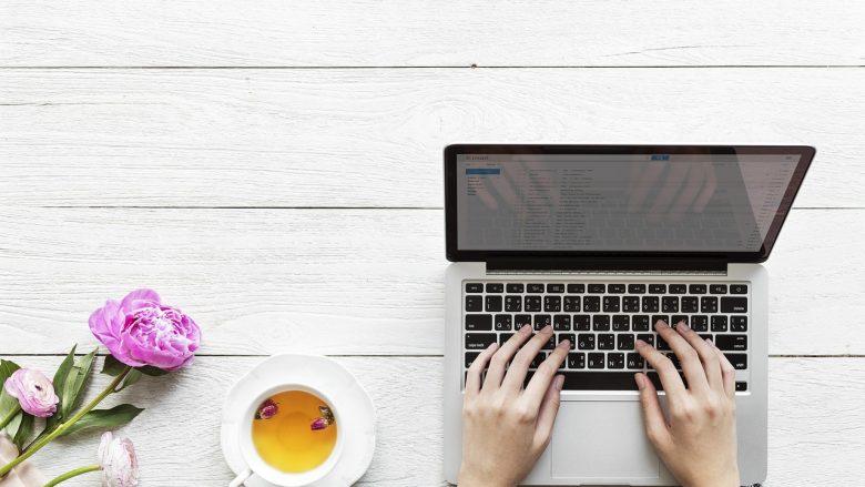 Bild zum Artiekl: Anschreiben Formalitäten Frau tippt etwas in den Laptop, Tasse steht daneben