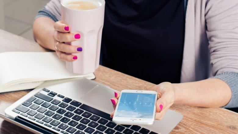 Bild zum Artikel PR/Öffentlichkeitsarbeit: Frau am Schreibtisch mit Laptop, Handy und Kaffee