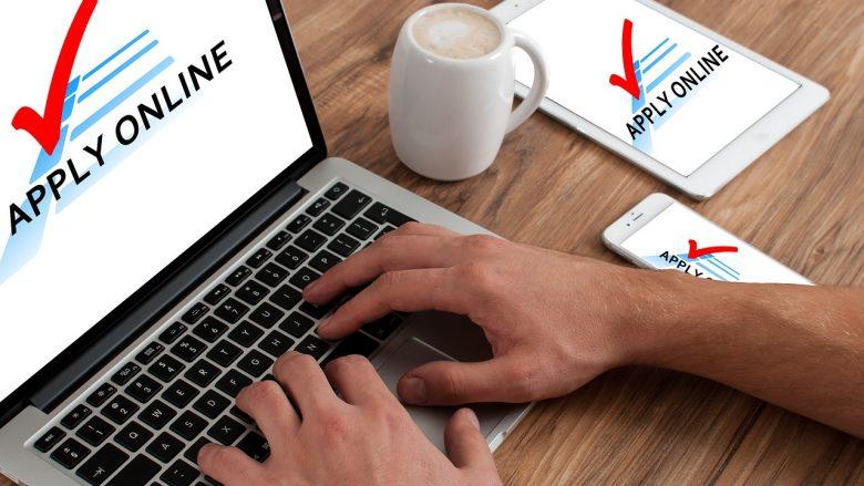 """Bild zum Artikel: Webformular. Tisch mit Laptop mit Aufschrift """"Apply Online"""", Tasse und Hände."""