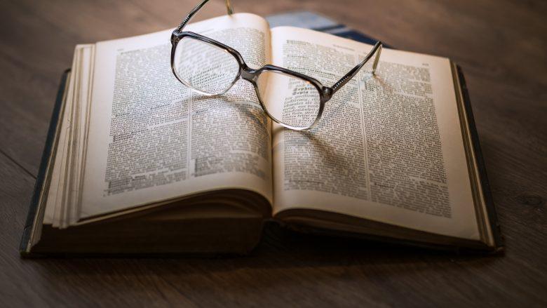 Bild zum Artikel Berufsfeld Wissenschaft: Tisch mit Buch und Brille
