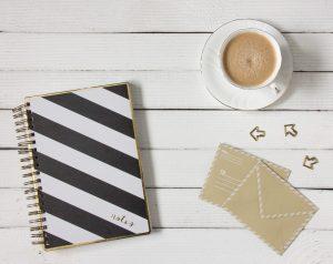 Notizblock liegt auf Tisch, daneben befindet sich eine Tasse Kaffee und zwei kleine Umschläge.