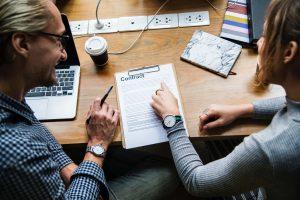 Zum Artikel HR und Personalwesen: 2 Personen am Tisch schauen auf Vertrag
